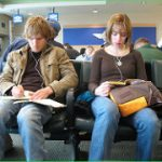 two twenty or so year olds sitting in airport on phones