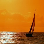 orange sunset over the sea with sail boat