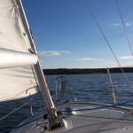 front of small sailboat heading towards land in distance